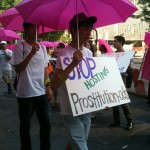 """Protestors with pink umbrellas and sign reading """"Stop Hosting Prostitution Ads"""" outside Backpage Office"""