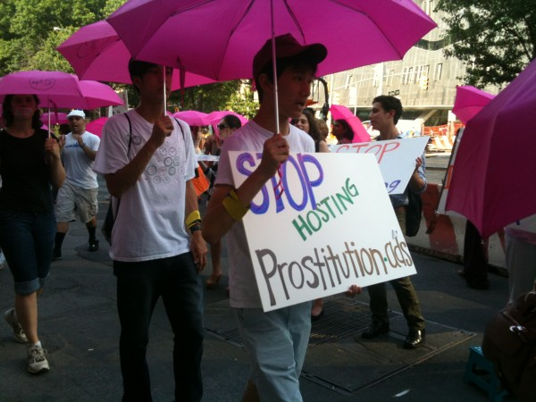"Protestors with pink umbrellas and sign reading ""Stop Hosting Prostitution Ads"" outside Backpage Office"