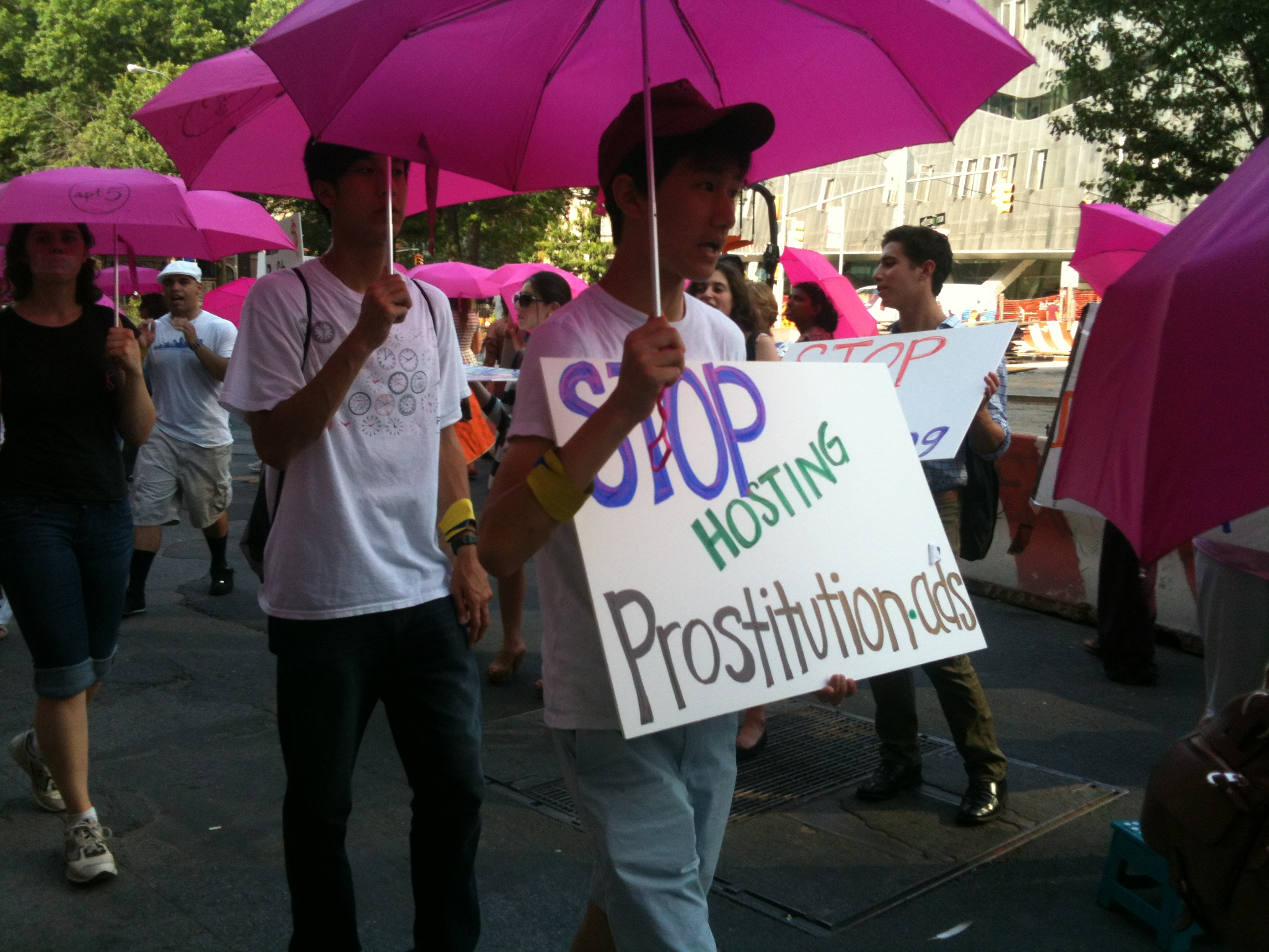 Protestors with pink umbrellas and sign reading