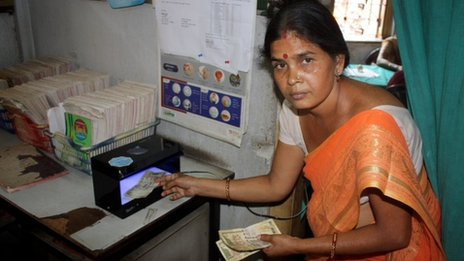 A  Durbar Mahila Samanwaya Committee member uses a device for detecting fake currency, made available to sex workers to check their clients' bills (Photo by BBC News)
