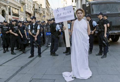"""A protester in Dora's hometown of Kusadasi holds up a sign reading """"Is It My Turn?"""" as riot police approach (Photo by AP Photo/Vadim Ghirda/Scanpix)"""