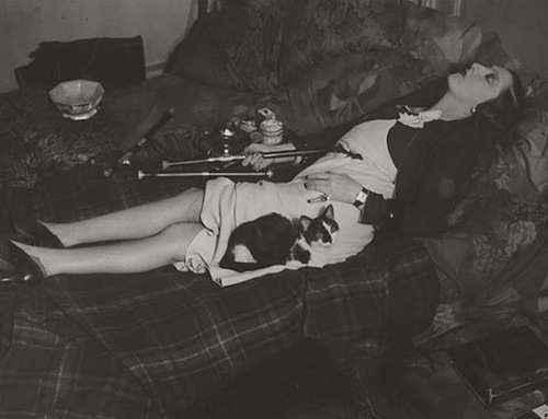 The madam of an opium den relaxing into a nod—note that is she is unbothered by clients as she does so. (One of a series of photographs by Hungarian photojournalist Brassaï taken in Paris in the early 1930s.)