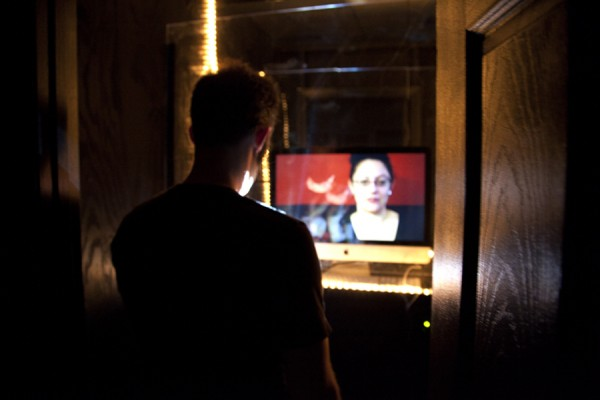 "The ""Peep Show"" section of Lauren Mccubbin's large-scale installation art project on the lives of sex workers, A Monument to the Risen, in which viewers put coins into a slot in order to watch video interviews with sex workers. Audacia Ray is on the screen in this photo. (Photo via artist's website)"