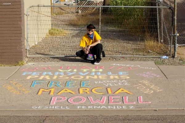 Peggy Plews of Arizona Prison Watch posing with chalk art (Photo by PJ Starr)